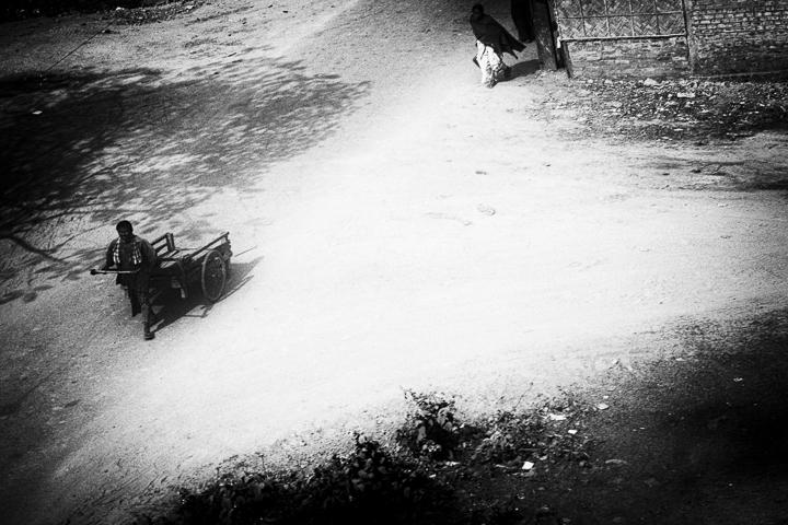 une homme tire une charrette dans la rue scene de vie photo contraste de Guy Monnet noir et blanc de la série Tamil nadu